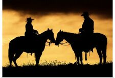 Poster Print Wall Art entitled Cowboy and cowgirl on horseback in silhouette at