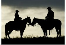 Poster Print Wall Art entitled Cowboy and cowgirl on horseback by lake at sunset