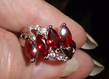 Silver shank (925) mark, 4 marquise shaped garnets,  6 white topaz accent stones