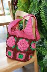 Crochet is a pink flower bag. Pink flowers are surrounded by green leaves.