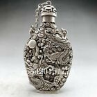 Ancient Tibetan silver snuff bottles are carved by hand with dragon designs.