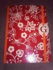 Redish orange floral notebook with G on cover